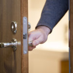 The hand of a man opens a door