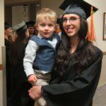 Mom graduates while holding child