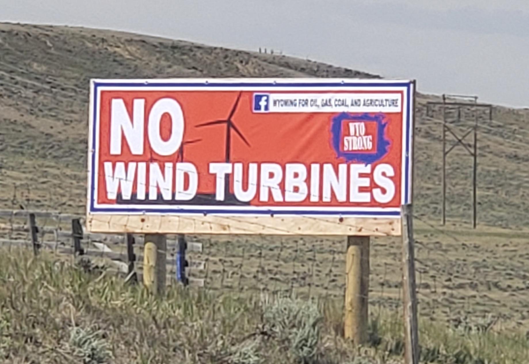 No Wind Turbines billboard stands in the field